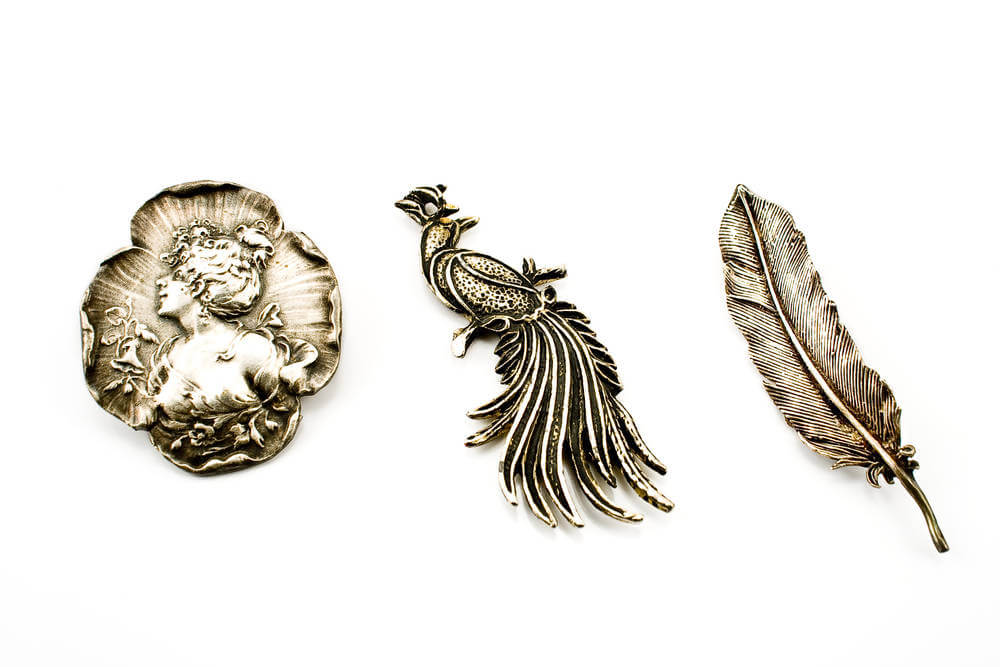 Three antique silver brooches isolated on white