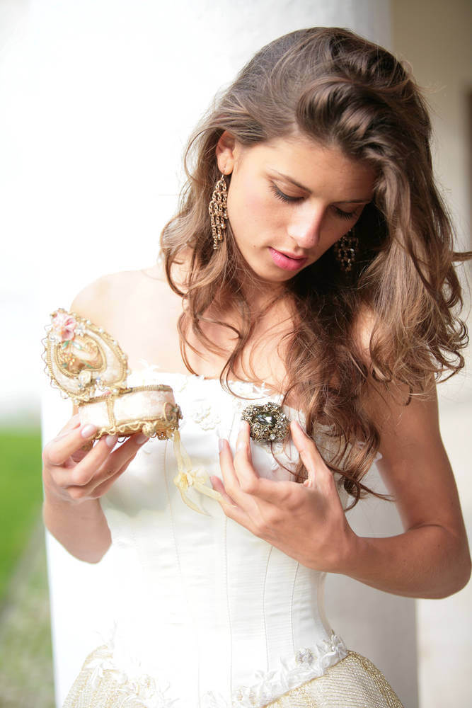 the beautiful girl in white-golden gown look at the gift